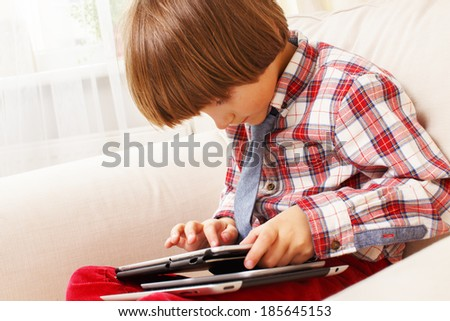 A boy holding a tablet pc in an armchair