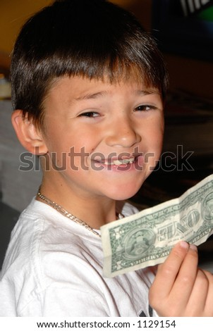 A boy holds up a dollar bill he found inside his birthday card.
