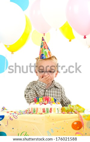 A boy in a party hat sitting by a birthday cake.