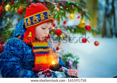 A boy in a red patterned knitted cap with ear-flaps and with a bright scarf holding a lantern with a burning candle and blowing out it near the decorated Christmas tree on a frosty winter day outdoor