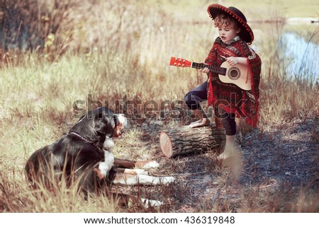 A boy in a sombrero sings and plays the guitar , and the dog hears - stock photo