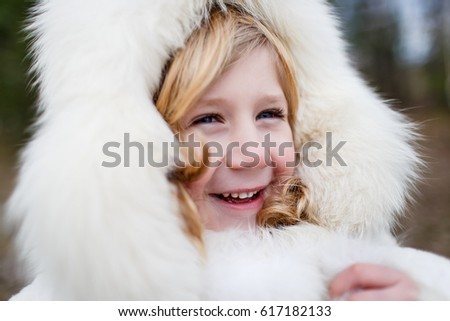 A boy in a white fur hat smiling and having fun