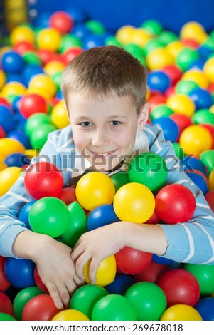 A boy in the playing room with many little colored balls. Close portrait