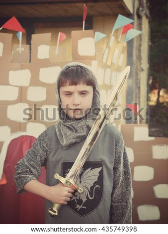 A boy is dressed up as a knight prince costumes with a sword looking next to a cardboard castle for a creative imagination concept.