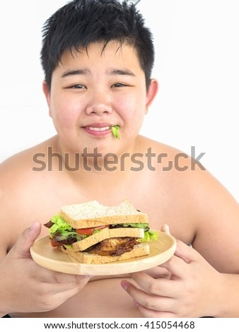 A boy is happily eat at sandwich. Photo is focused at sandwich. - stock photo