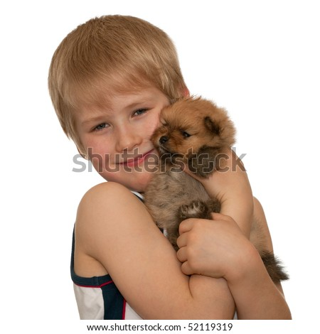 A boy is holding a little puppy; isolated on the white background