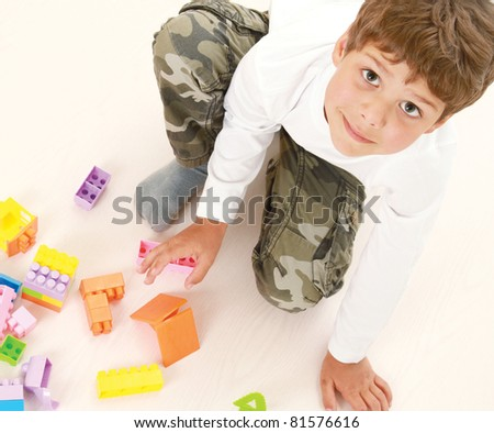 A boy is playing with lego looking up,  isolated on white, top view