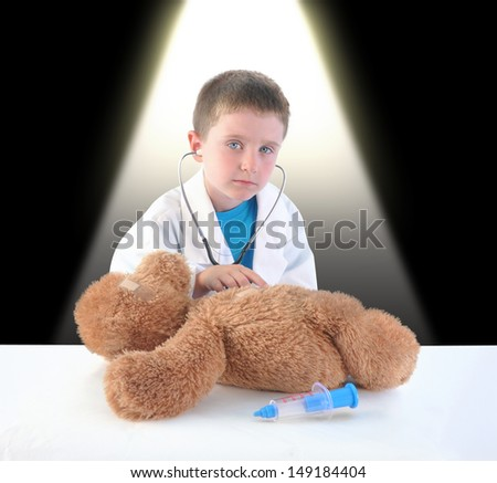 A boy is pretending to be a doctor and has a checkup exam on a toy teddy bear. The child has a stethoscope. - stock photo