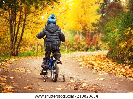 A boy is riding on a bike in autumn day - stock photo