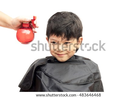 A boy is sprayed his hair by hair dresser isolated over white background