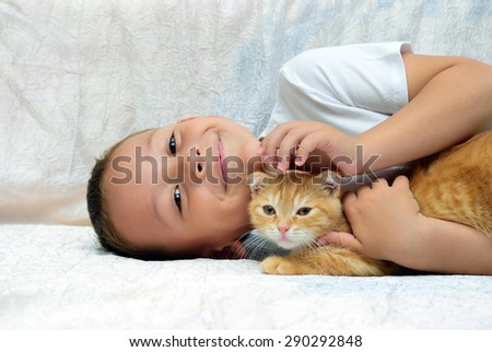 A boy lies and embraces a kitten - stock photo
