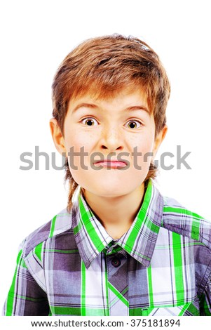 A boy looks at the camera and makes faces. Isolated over white. - stock photo