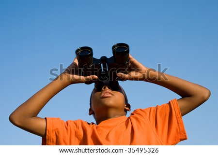 a boy looks skywards through binoculars - stock photo