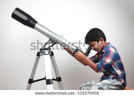 A boy looks through a telescope - stock photo