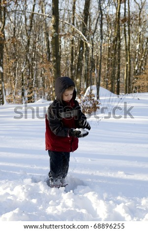 A boy makes a snowball - stock photo