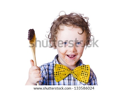 A boy messing with food holding a spoon on a white background