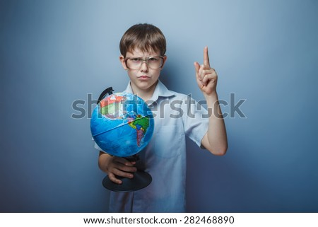A boy of about ten European appearance in light brown shirt and glasses holding a globe and raised his index finger up on a gray background, discovery, scientist - stock photo