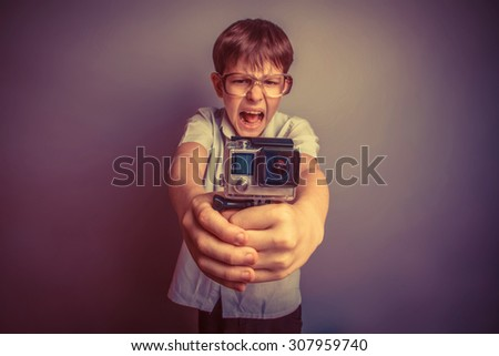 A boy of about ten European appearance in light brown shirt and glasses holding a small camera action and shouts against the gray background, video  GoPro, screaming, go pro camera retro - stock photo