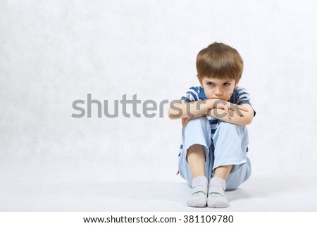 A boy of six years old show that he is angry with others on a white background  . Free space for a text.