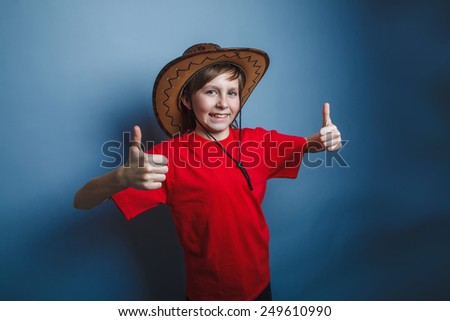 a boy of twelve European appearance cowboy hat, a gesture so hands on a gray background - stock photo