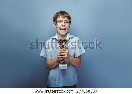 a boy of 10 years of European appearance with glasses holding a cup in his hands on a gray background