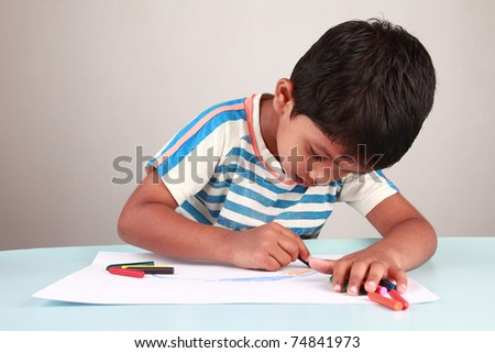 A boy painting on a white paper - stock photo