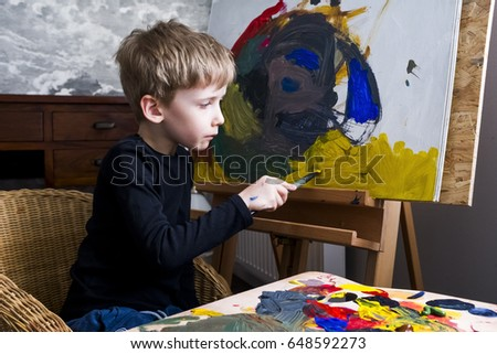 A boy painting on easel. Painting with acrylic.