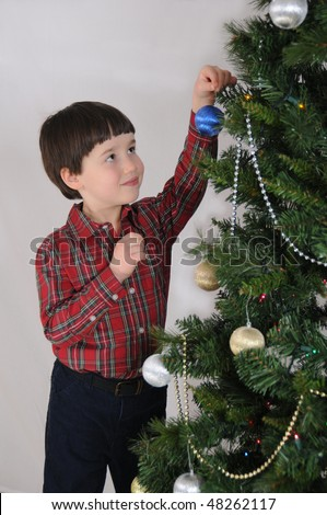 A boy places an ornament on a Christmas tree - stock photo