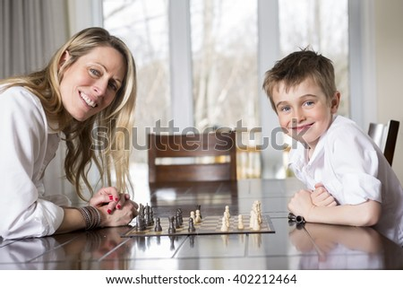 A boy playing chess at home with mother - stock photo