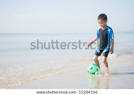 A boy playing football at the beach - stock photo