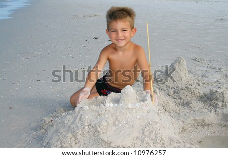 A boy playing in the sand on the beach