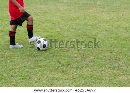 A boy playing soccer on the sports field