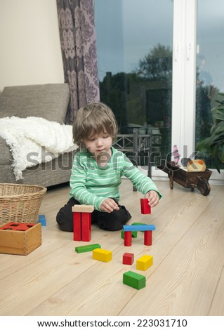 a boy playing with wooden blocks on the floor in the living room at home - stock photo