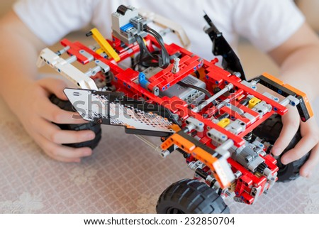 A boy plays collects from the constructor of the car - stock photo