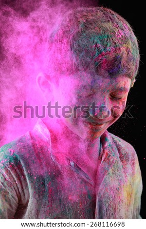 A boy plays Holi with colored powder exploding around his face in a dark background. - stock photo