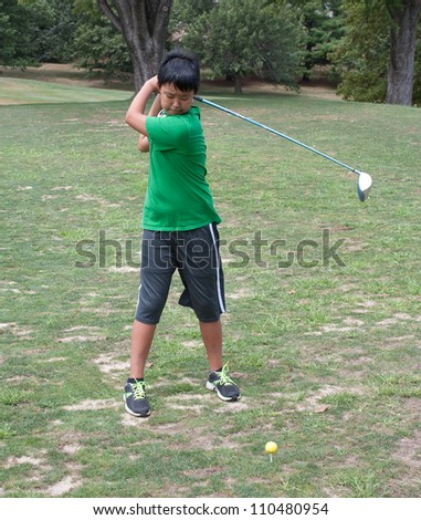 A boy practicing his golf swing at the driving range - stock photo