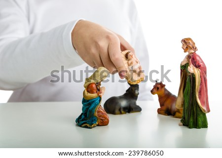 A boy put the statue of the Infant Jesus completing a Christmas Crib where the little statues represent the Holy Family: the Virgin Mary, Saint Joseph and the infant Jesus, watched by ox and donkey - stock photo