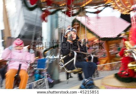 A boy rides a fair carousel evening - stock photo