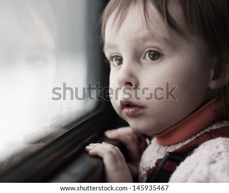 A boy rides on a train and looking out the window.