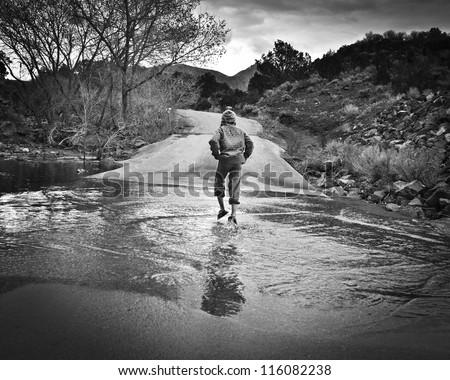 A boy runs through a flooded spillway at Baker Reservoir, Utah. - stock photo