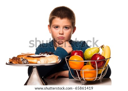 a boy's choice of a healthy or unhealth snack - stock photo