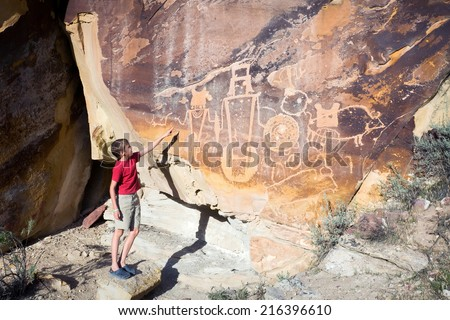 A boy shows his hand on the wall with petroglyphs. Dinosaur National Monument (USA. Utah) - stock photo