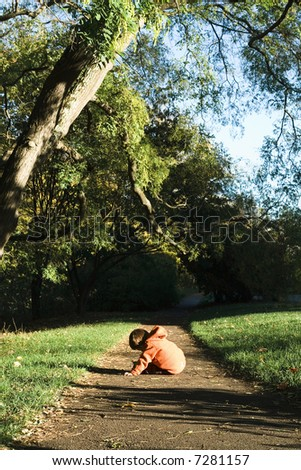 A boy sits and observes nature on a path in a park. - stock photo