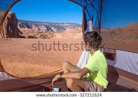 A boy sits at the entrance to the tent and looking at the beautiful wild landscape of rocky desert. Grand Staircase-Escalante National Monument, Utah - stock photo