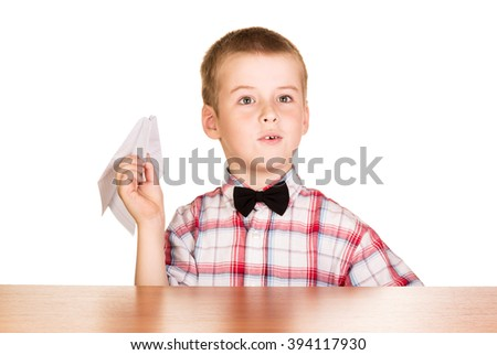 A boy sits at the table and holding a paper airplane isolated on white background. - stock photo