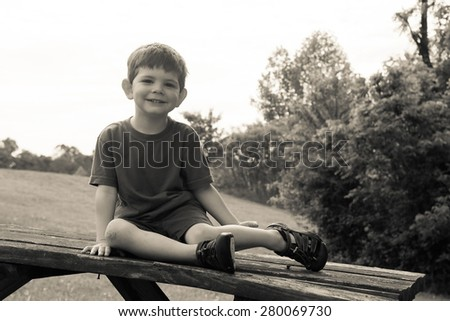 A boy sitting on a bench outside at the park. Black and white, horizontal.  - stock photo