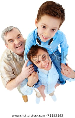 A boy sitting on his father?s shoulders with a grandfather standing by them - stock photo
