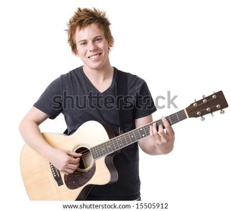 A boy smiles as he plays a guitar - stock photo