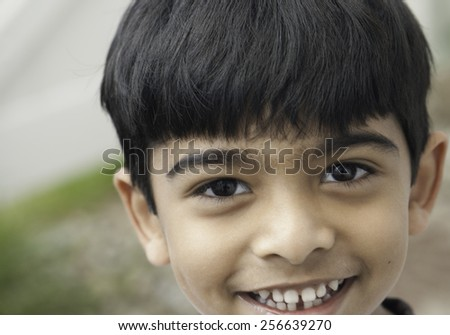 A boy smiling at camera in out door - stock photo