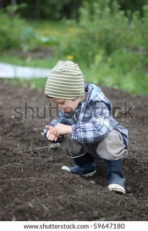A boy sowing  seeds in soil